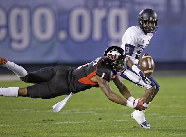 Northern Illinois safety Dechane Durante, front, breaks up a pass intended for Utah State receiver Bruce Natson during the first half of the Poinsettia Bowl NCAA college football game Thursday, Dec. 26, 2013, in San Diego. (AP Photo/Lenny Ignelzi)