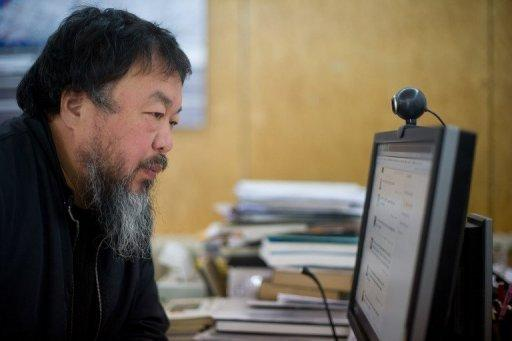 "Chinese artist Ai Weiwei sits at a computer at his Beijing office in April 2012. The dissident artist has accused Chinese authorities of trying to ""crush him"" after he was barred from a hearing challenging a multi-million-dollar tax penalty against a firm he founded"