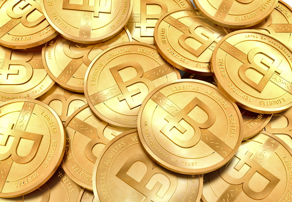 A pile of glittering gold coins, all embossed with the Bitcoin logo