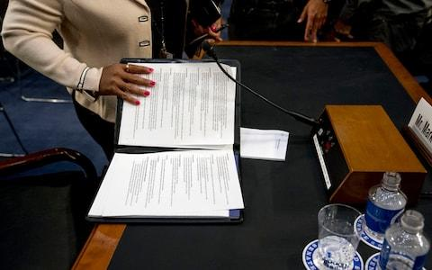 An aide to Facebook CEO Mark Zuckerberg closes a binder of notes left on the table - Credit: AP