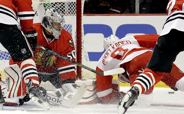 Chicago Blackhawks goalie Corey Crawford, left, blocks a shot by Detroit Red Wings' Justin Abdelkader (8) during the first period of an NHL hockey game in Chicago, Sunday, March 16, 2014. (AP Photo/Nam Y. Huh)