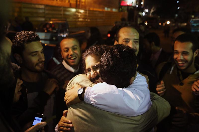 Alaa Abdel-Fattah, center in white, a prominent activist and a leading figure in the 2011 uprising against Egyptian autocrat Hosni Mubarak, is welcomed after he was released from the main central security office in Cairo, Egypt, Sunday, March 23, 2014. Abdel-Fattah was arrested from his home on Nov. 28, 2013, and he and his wife accuse police of attacking them during the arrest. Egyptian court on Sunday ordered the release on bail pending trial of Abdel-Fattah charged with breaking a new law that heavily restricts protests, after he spent nearly four months in jail. (AP Photo/Roger Anis, El Shorouk Newspaper) EGYPT OUT