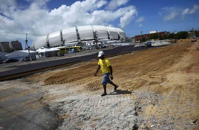 A worker, wearing a Brazilian football jersey, strolls through a construction site next to the Dunas arena soccer stadium in Natal, June 12 , 2014. Mexico will face Cameroon in their 2014 World Cup football match here on June 13. REUTERS/Dylan Martinez (BRAZIL - Tags: BUSINESS CONSTRUCTION SOCCER SPORT WORLD CUP)