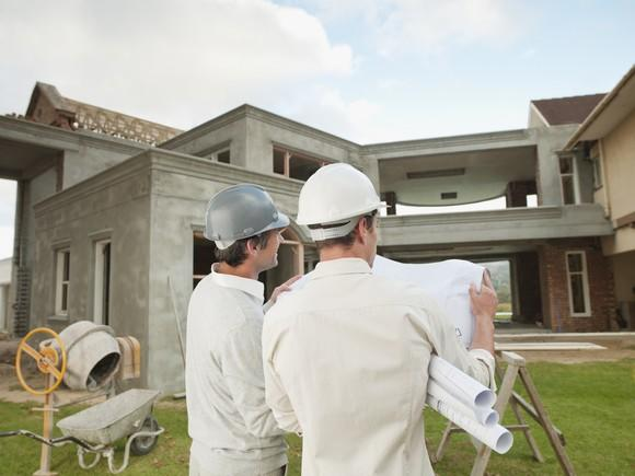 Men in hard hats reading blueprints in front of a house