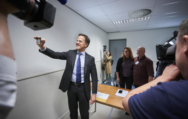 Netherlands Prime Minister Mark Rutte takes a photo on a phone at a polling station in The Hague, Netherlands, Thursday, May 23, 2019, as polls opened in elections for the European Parliament. (AP Photo/Phil Nijhuis)