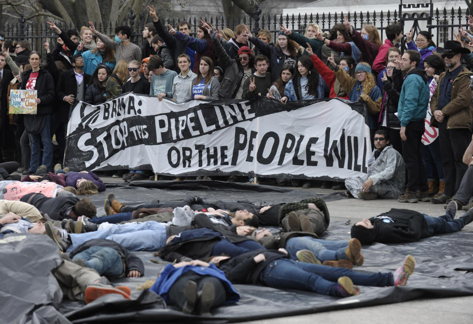 FILE - In this March 2, 2014, file photo, several hundred students and youth who marched from Georgetown University to the White House to protest the Keystone XL Pipeline wait to be arrested outside the White House in Washington. The sponsor of the Keystone XL crude oil pipeline says it's pulling the plug on the contentious project, Wednesday, June 9, 2021, after Canadian officials failed to persuade the Biden administration to reverse its cancellation of the company's permit. . (AP Photo/Susan Walsh, File)