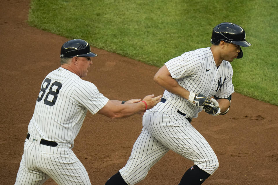 New York Yankees' Giancarlo Stanton, right, celebrates with third base coach Phil Nevin as he runs the bases after hitting a two-run home run during the first inning of a baseball game against the Houston Astros Tuesday, May 4, 2021, in New York. (AP Photo/Frank Franklin II)