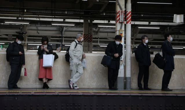 People wearing protective face masks, following an outbreak of the coronavirus, await for their train at the Tokyo station in Tokyo