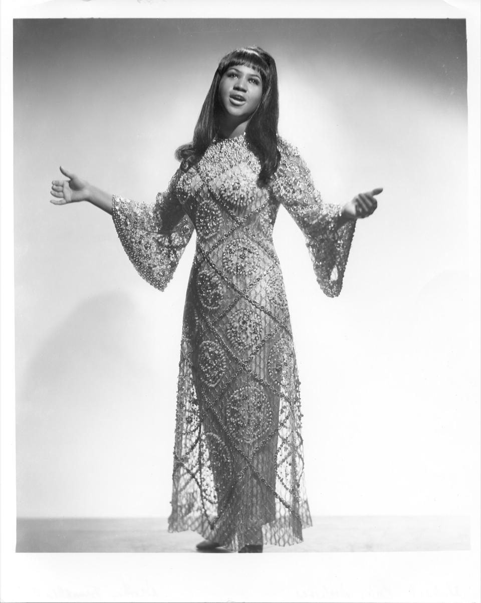 <p>Aretha Franklin wears an intricately beaded maxi gown and flowing strands with blunt bangs while posing for a portrait. (Photo by Michael Ochs Archives/Getty Images) </p>