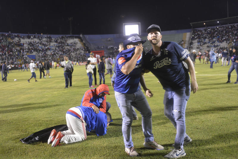 Soccer fans are affected by tear gas that was fired by police trying to break up a deadly fight that broke out between fans before the start of a game between Motagua and Olimpia, inside the national stadium in Tegucigalpa, Honduras, late Saturday, Aug. 17, 2019. The fight between fans of rival soccer teams outside the stadium left three people dead and led to the suspension of the game. (Victor Colindres/La Tribunal via AP)