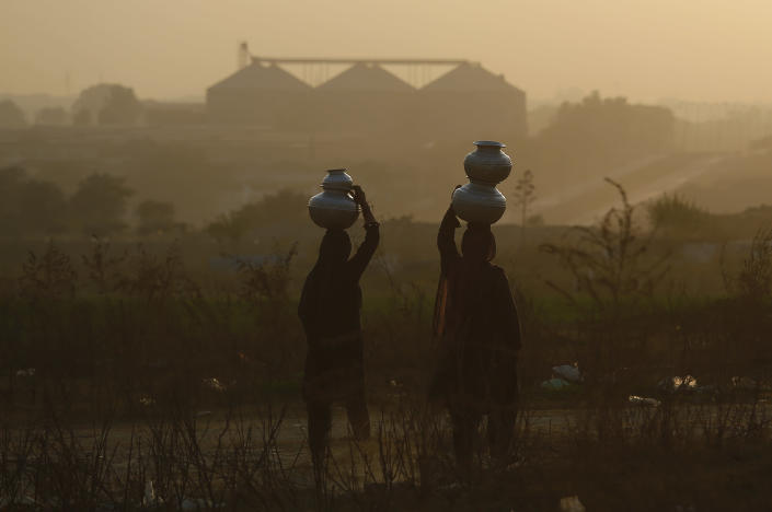 Pakistani nomad women carry water to their houses in a hazy evening on the outskirts of Islamabad, Pakistan, Tuesday, Dec. 4, 2018. The COP 24 UN Climate Change Conference is taking place in Katowice, Poland where negotiators from around the world are meeting for talks on curbing climate change. (AP Photo/Anjum Naveed)