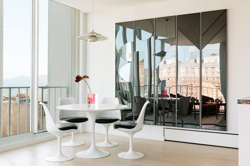 The minimalist breakfast nook features an Eero Saarinen tulip table and set of chairs from Design Within Reach, and the large-scale work by German artist Claudia Weiser reflects the city views.