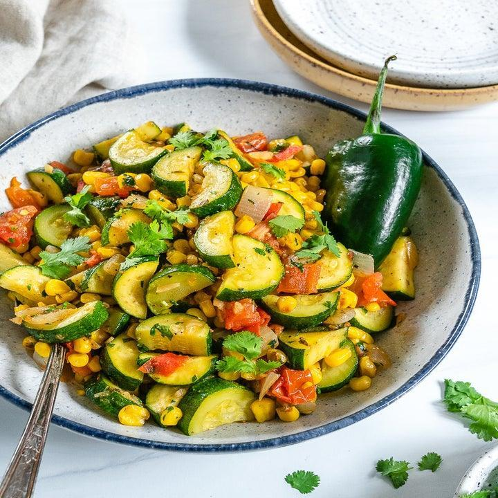 A bowl of cut zucchini, corn, and other colorful ingredients