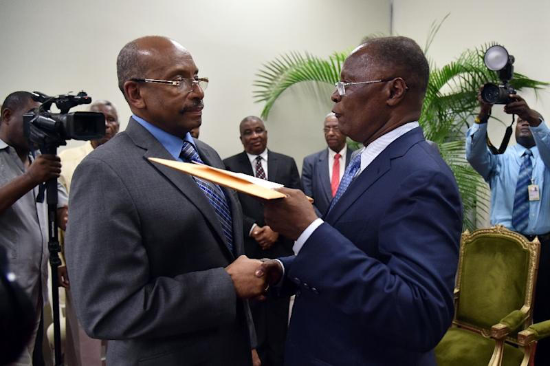 Haitian Provisional President Jocelerme Privert (R) talks to President of the Provisional Electoral Council Leopold Berlanger (L) after a special commission's investigative report on the 2015 Haitian election in Port-au-Prince, on May 30, 2016