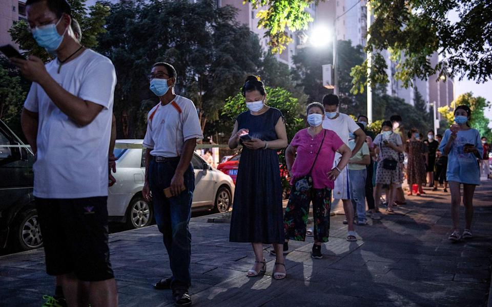 Residents queue to test for the Covid-19 in Wuhan - AFP