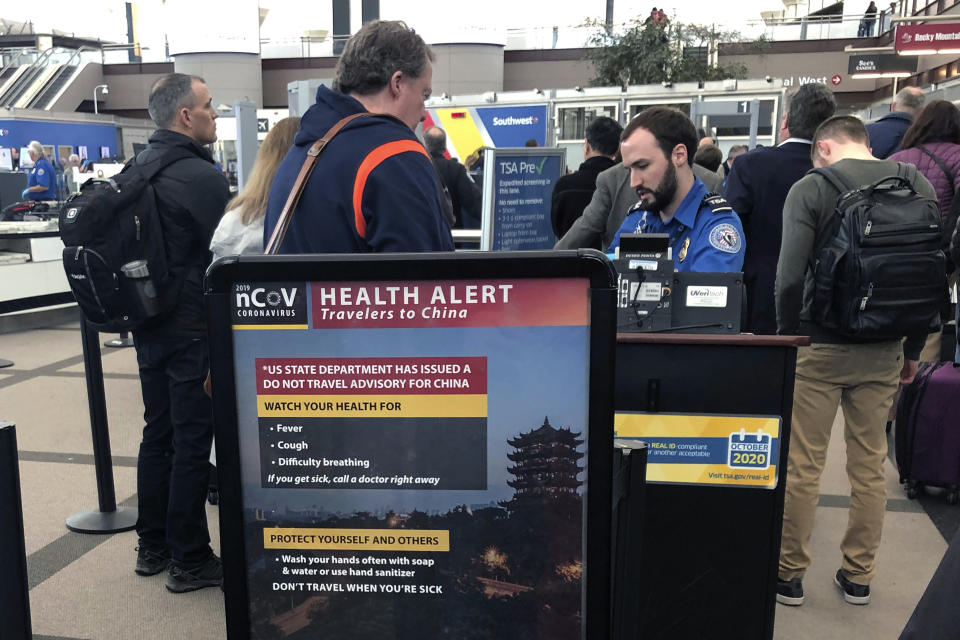 "FILE - In this Monday, March 2, 2020 file photo, a health alert for people traveling to China is shown at a Transportation Security Administration security checkpoint at the Denver International Airport in Denver. President Donald Trump has repeatedly credited his February ban on travelers from mainland China as his signature move against the advance of the coronavirus pandemic -- a ""strong wall"" that allowed only U.S. citizens inside, he boasted in May. But Trump's wall was more like a sieve. Exempted were thousands of residents of the Chinese territories of Hong Kong and Macau. (AP Photo/Charles Rex Arbogast, File)"