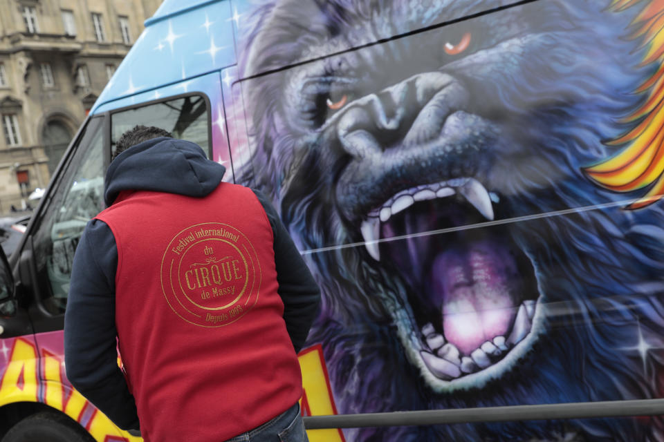 """A circus worker stands by a circus van during a protest Tuesday, Jan.26, 2021. French lawmakers start debating Tuesday a bill that would ban using wild animals in traveling circuses and keeping dolphins and whales in captivity in marine parks, amid other measures to better protect animal welfare. Circus workers stage a protest outside the National Assembly to denounce what they consider """"a mistake."""" (AP Photo/Lewis Joly)"""
