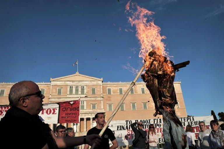 Protesters burn an effigy of a Greek worker in front of the parliament in Athens on April 28, 2013