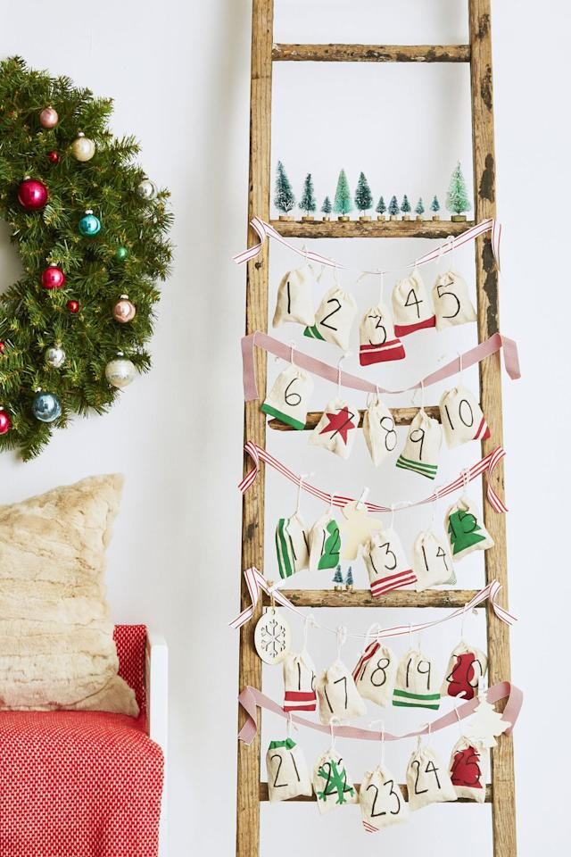 """<p>Instead of opening a flimsy cardboard box, hang up a DIY Advent calendar on a ladder or the tree. Decorated <a href=""""https://www.amazon.com/Cotton-Muslin-Bags-Drawstring-Count/dp/B00A4GRZNK/"""" target=""""_blank"""">muslin craft bags</a> conceal treats, toys, and messages from Santa—and you can fill them again next year, too.</p>"""