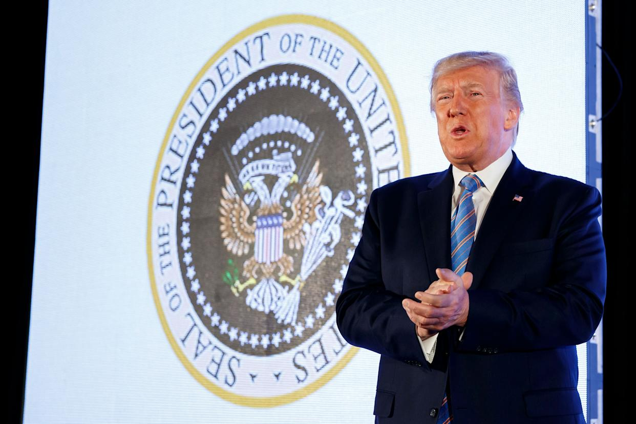 President Donald Trump speaks to a college Republican group as the doctored presidential seal showing Russian symbols and golf clubs is projected behind him. (Photo: ASSOCIATED PRESS)