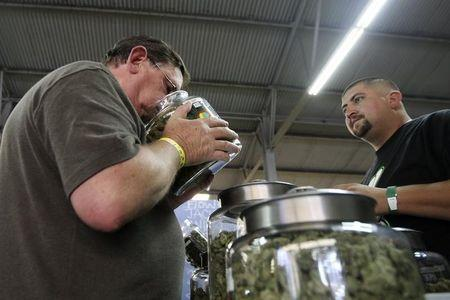 A medical marijuana user smells a jar of marijuana at the medical marijuana farmers market in Los Angeles