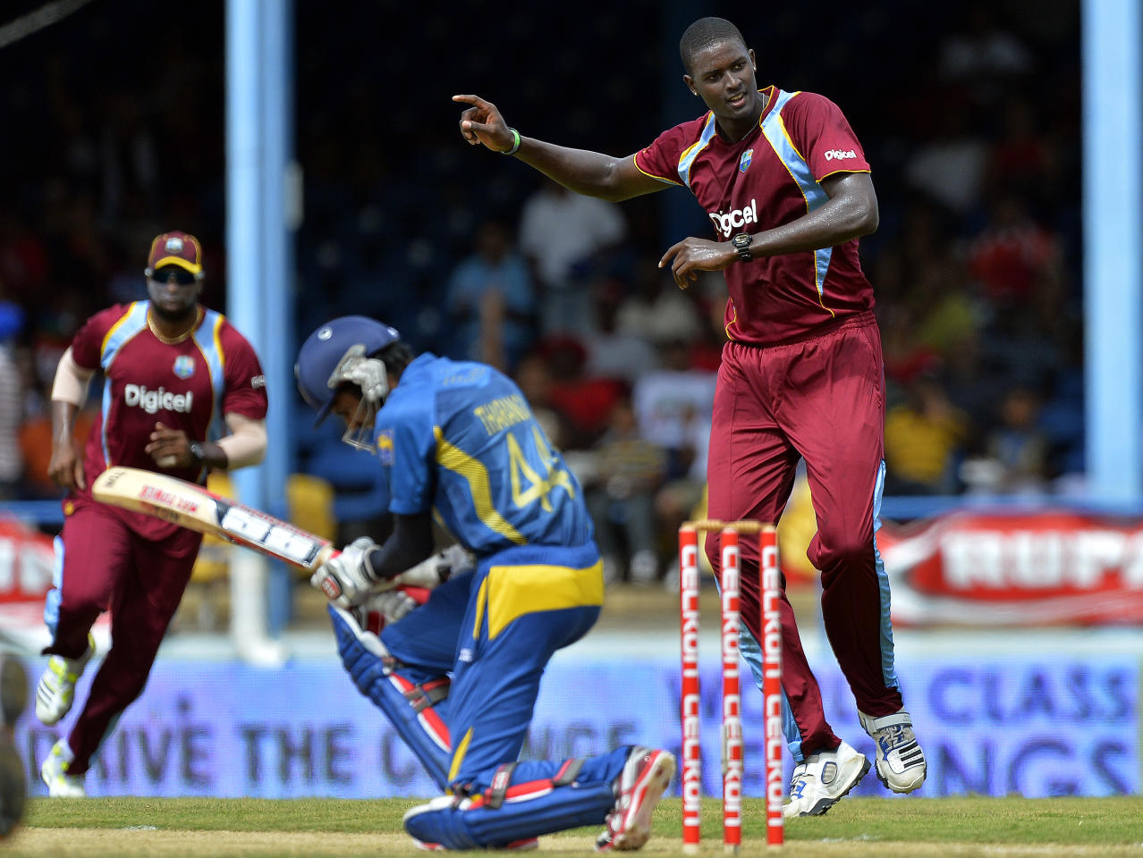 West Indies bowler Jason Holder (R) celebrates dismissing Sri Lankan batsman Upul Tharanga (L) during the fifth match of the Tri-Nation series between Sri Lanka and West Indies at the Queen's Park Oval in Port of Spain on July 7, 2013. West Indies won the toss and elected to field. AFP PHOTO/Jewel Samad