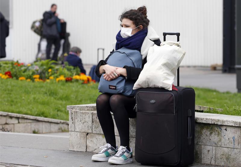 PARIS, FRANCE - MARCH 17: Passenger wearing a protective mask waits for a train at the Montparnasse station as many Parisians come to the stations of the capital to try to take a train and reach the province on March 17, 2020 in Paris, France. After the announcement of a general confinement due to an outbreak of coronavirus pandemic (COVID-19) announced by Emmanuel Macron on Monday evening, from today at noon for at least two weeks, the French will have to stay at home, under penalty of sanctions, unless travel is absolutely necessary, announced the head of state. President launched the war against the coronavirus and placed France in containment without ever saying the word. The Coronavirus epidemic has exceeded 7,500 dead for more than 189,000 infections across the world. (Photo by Chesnot/Getty Images)