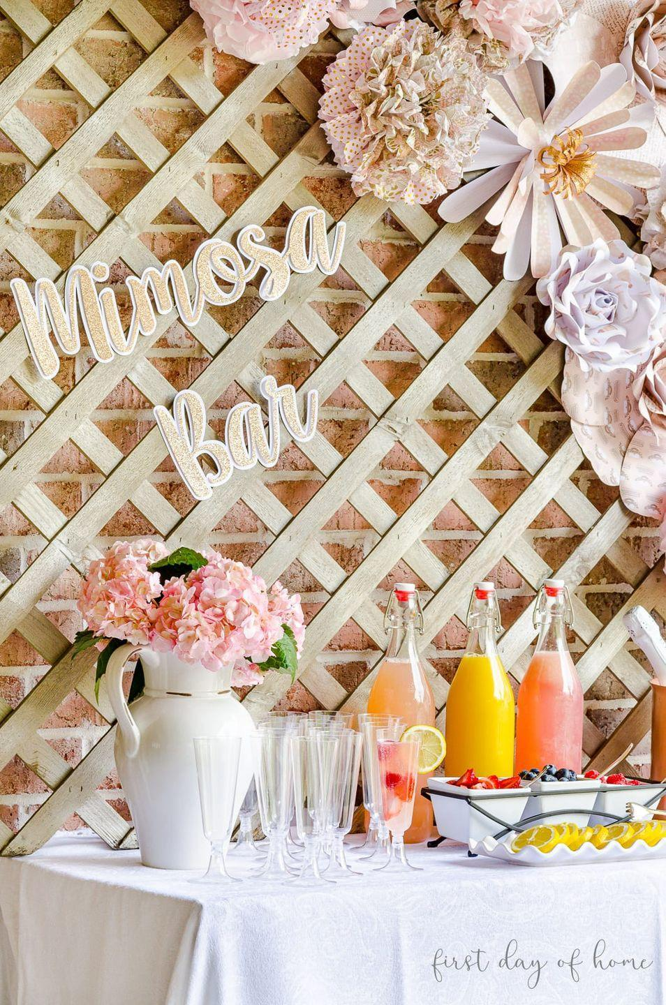 "<p>Not feeling a bar cart? Use a spare table to really spread out your mimosa-making station. Add a white table cloth and vase full of flowers for a chic touch. If you want to go all out, add a glittery sign that lets folks know where the mimosa bar is at.</p><p>See more at <a href=""https://www.firstdayofhome.com/mimosa-bar-ideas/"" rel=""nofollow noopener"" target=""_blank"" data-ylk=""slk:First Day of Home"" class=""link rapid-noclick-resp"">First Day of Home</a>.</p>"
