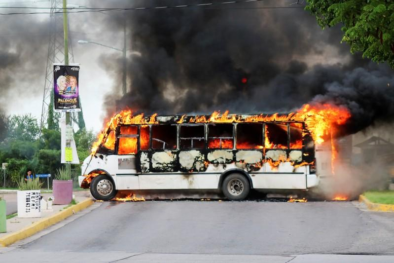 "A burning bus, set alight by cartel gunmen to block a road, is pictured during clashes with federal forces following the detention of Ovidio Guzman, son of drug kingpin Joaquin ""El Chapo"" Guzman, in Culiacan"