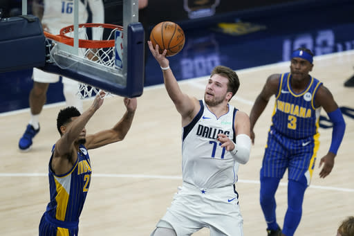 Dallas Mavericks' Luka Doncic (77) puts up a shot against Indiana Pacers' Jeremy Lamb (26) during the second half of an NBA basketball game, Wednesday, Jan. 20, 2021, in Indianapolis. (AP Photo/Darron Cummings)