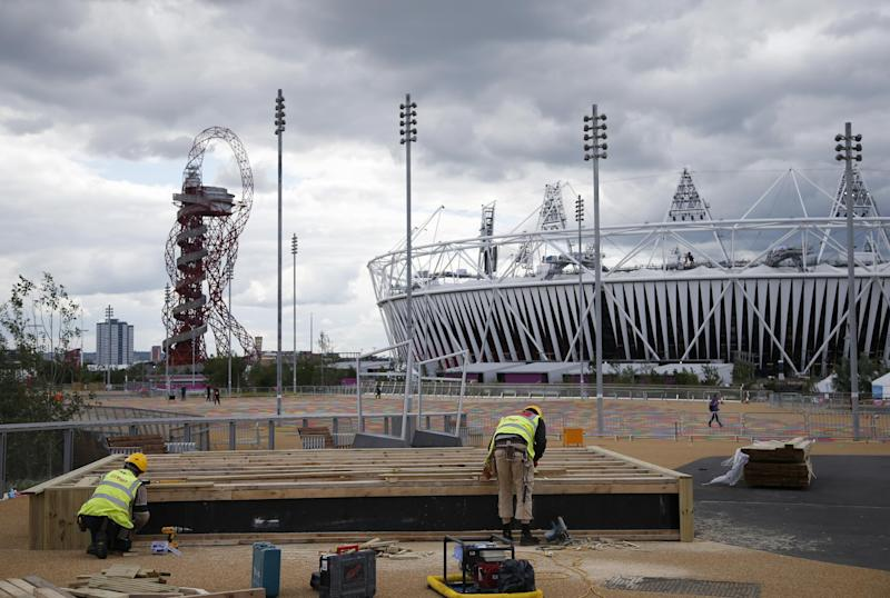Construction crews work outside the Olympic Stadium as preparations continue for the 2012 Summer Olympics, Sunday, July 15, 2012, in London. At left is the Orbit. (AP Photo/Jae Hong)