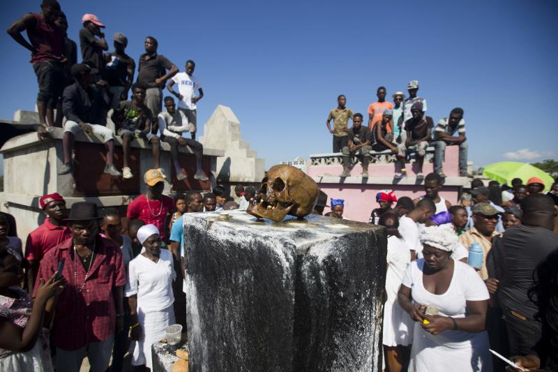 In this Nov. 1, 2018 photo, a human skull sits on top of Baron Samedi's tomb during the annual Voodoo festival Fete Gede at Cite Soleil Cemetery in Port-au-Prince, Haiti. With the faces covered with white-powder, wearing hats and black, white and purple clothes, voodoo believers in Haiti walk through the streets and visit the cemeteries along the country during the Fete Gede, a celebration of the spirits equivalent to the Roman Catholic festivity of the Day of All Saints. (AP Photo/Dieu Nalio Chery)