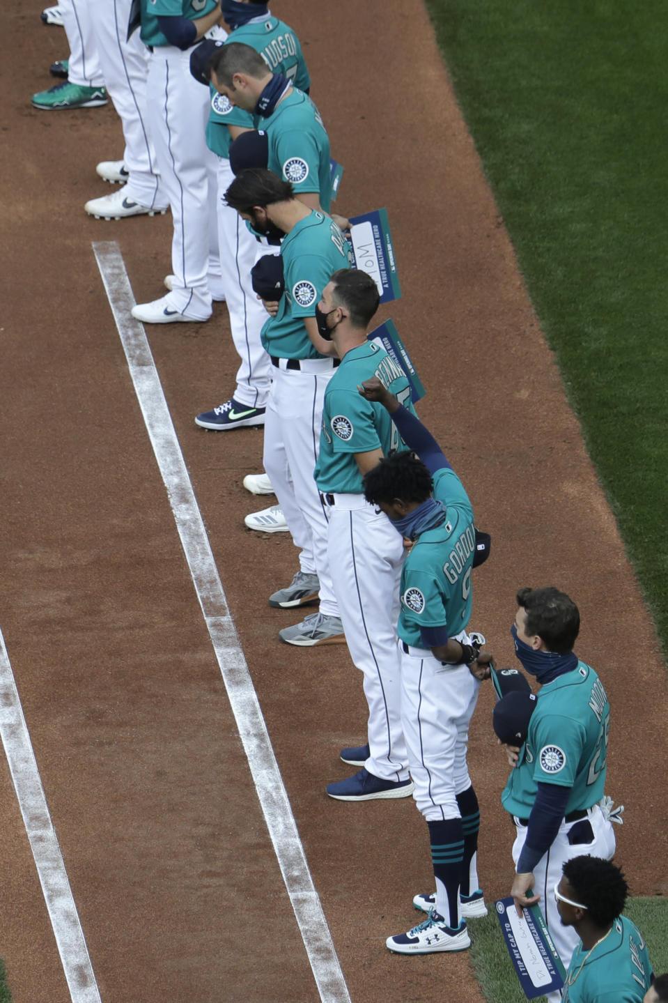 Seattle Mariners left fielder Dee Gordon (9) raises his fist during the singing of the national anthem before the Mariners' home opener baseball game against the Oakland Athletics, Friday, July 31, 2020, in Seattle at T-Mobile Park. (AP Photo/Ted S. Warren)
