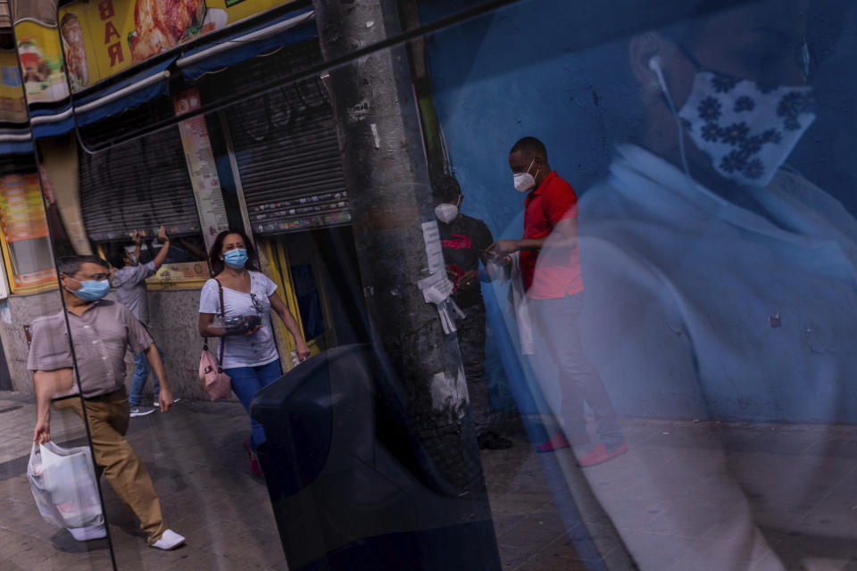 Pedestrians wear face masks to prevent the spread of coronavirus in the southern neighborhood of Vallecas in Madrid, Spain, Wednesday, Sept. 16, 2020. Spain has become the first western Europe to accumulate more than 1 million confirmed infections as the country of 47 million inhabitants struggles to contain a resurgence of the coronavirus. (AP Photo/Bernat Armangue)
