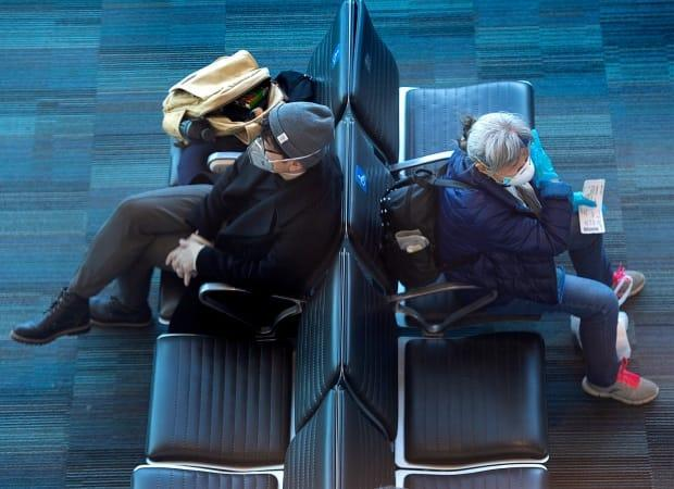 Passengers wear protective gear as they wait for a flight at Halifax Stanfield International Airport in Enfield, N.S. on Monday, March 16, 2020.