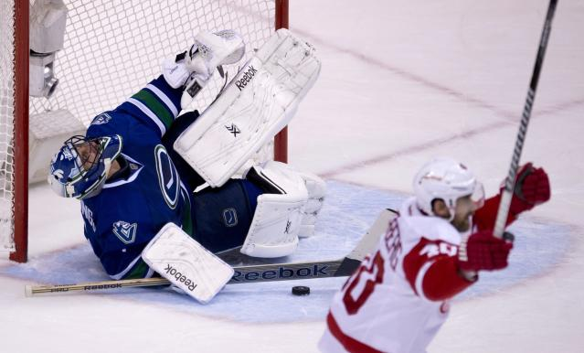 Detroit Red Wings center Henrik Zetterberg (40) celebrates teammate Tomas Tatar's goal past Vancouver Canucks goalie Roberto Luongo (1) during the second period of an NHL hockey game in Vancouver, British Columbia, Wednesday, Oct. 30, 2013. (AP Photo/The Canadian Press, Jonathan Hayward)