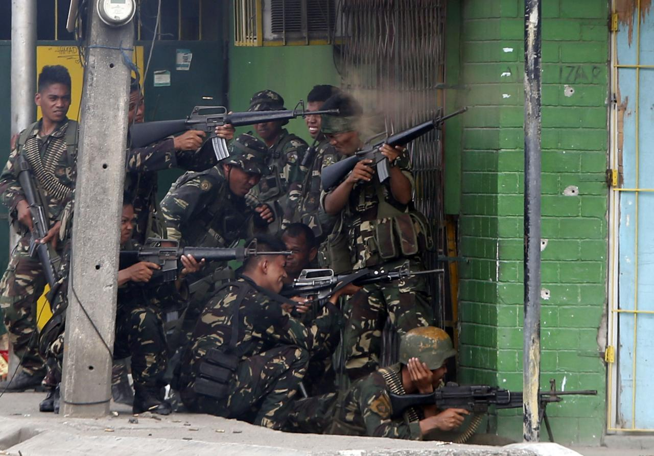 Government soldiers fire their weapons towards positions held by Muslim rebels from the MNLF during a firefight in Zamboanga city, in southern Philippines