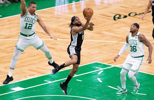 San Antonio Spurs guard Patty Mills (C) lays up the ball after getting past defending Boston Celtics forward Grant Williams (L) and Boston Celtics guard Marcus Smart (R) during the first half of the NBA basketball game between the San Antonio Spurs at Boston Celtics at the TD Garden in Boston, Massachusetts, USA, 08 January 2020. EFE/EPA/CJ GUNTHER
