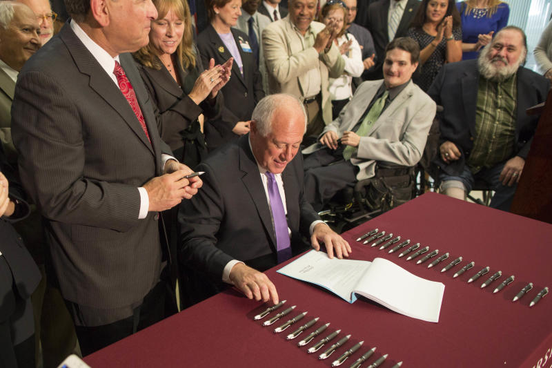 Illinois Gov. Pat Quinn signs a bill for medical marijuana at the University of Chicago Center for Care and Discovery in Chicago, Thursday, Aug. 1, 2013. The measure outlines a four-year pilot program that requires patients and caregivers to undergo background checks and sets provisions for state-regulated dispensaries. The proposal says patients can be allowed up to 2.5 ounces at a time. (AP Photo/Scott Eisen)