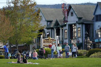 Visitors gather at a waterfront park, Saturday, May 15, 2021, in Bar Harbor, Maine. Gov. Janet Mills is is eliminating most outdoor distancing requirements imposed during the COVID-19 pandemic as the tourism season begins to kick into gear. (AP Photo/Robert F. Bukaty)