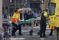 <p>Mossos d'Esquadra Police officers and emergency service workers move an injured after a van crashes into pedestrians in Las Ramblas, downtown Barcelona, Spain, August 17, 2017. (Quique Garcia/EPA/REX/Shutterstock) </p>