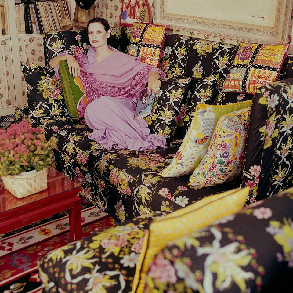 <p>Vanderbilt posing for <em>Vogue</em> in 1975 in the apartment she shared with her husband, Wyatt Cooper, and her two sons. She designed the floral pillows on the sofa. <br></p>