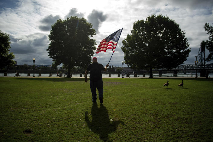 A member of the Proud Boys, who declined to give his name, carries a flag before the start of a protest in Portland, Ore., on Saturday, Aug. 17, 2019. Police have mobilized to prevent clashes between conservative groups and counter-protesters who plan to converge in the city. (AP Photo/Noah Berger)