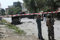 Afghan security personnel stand guard near a charred vehicle from which rockets were fired that landed near the Afghan presidential palace in Kabul