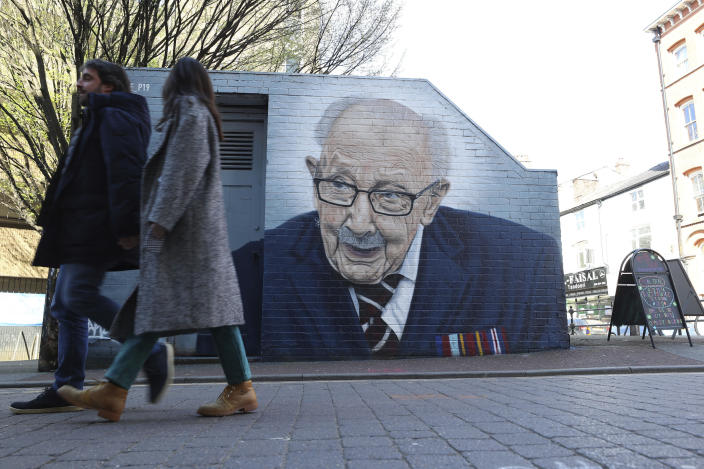 People walk past a mural of Captain Tom Moore by by street artist Akse P19 in Manchester's North Quarter, England, Friday April 2, 2021. (Peter Byrne/PA via AP)