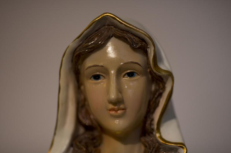 "A statue of the Virgin Mary, that residents say ""weeps"" oil, has attracted thousands of visitors in the last week to an apartment belonging to the Khoury family, in Tarshiha, a small Israeli town near the Lebanon border,Tuesday, Feb. 11, 2014. The family says it is most striking when a ""tear"" seems to roll down the statue's cheek. Parts of the statue appear to be slick with moisture, even after it is wiped off. (AP Photo/Ariel Schalit)"