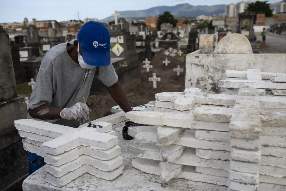 A cemetery worker paints numbers on crosses to be used as grave markers, at the Inahuma cemetery in Rio de Janeiro, Brazil, Wednesday, April 28, 2021, amid the new coronavirus pandemic. (AP Photo/Bruna Prado)