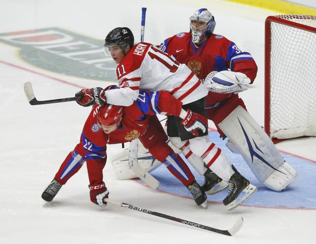 Canada's Bo Horvat (C) leans over Russia's Andrei Mironov (L) as Russia's goalie Andrei Vasilevski tries to follow the play during the second period of their IIHF World Junior Championship ice hockey game in Malmo, Sweden, January 5, 2014. REUTERS/Alexander Demianchuk (SWEDEN - Tags: SPORT ICE HOCKEY)