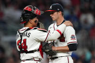 Atlanta Braves catcher William Contreras (24) talks with pitcher Tucker Davidson during the fifth inning of the team's baseball game against the New York Mets on Tuesday, May 18, 2021, in Atlanta. (AP Photo/John Bazemore)