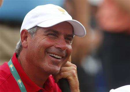 U.S. team captain Fred Couples laughs on the 18th green during the four ball matches at the 2013 Presidents Cup golf tournament at Muirfield Village Golf Club in Dublin, Ohio